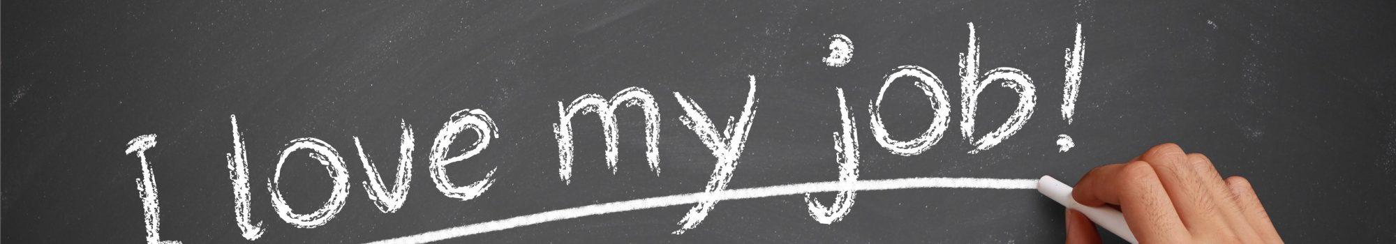 Hand with white chalk writing 'I love my job!' on chalkboard.