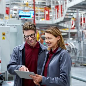 Smiling engineers using digital tablet by control panel. Confident workers are in uniform at automobile industry. Male and female professionals are working at car plant.